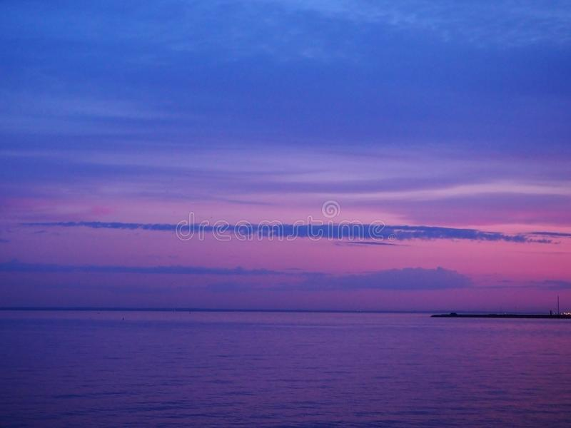 Schemering multi-colored roze en blauwe hemel bij de zonsondergang met kleurrijke bezinning in het zeewater Panoramisch marien la stock afbeelding