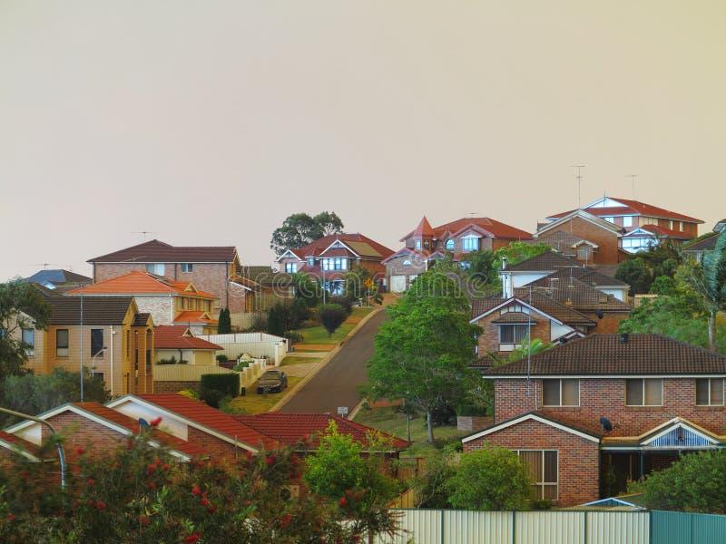 Schemering over moderne huizen door bushfires stock afbeeldingen