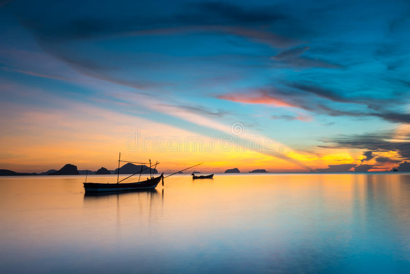 Schemeringhemel en silhouet vissersboot stock foto
