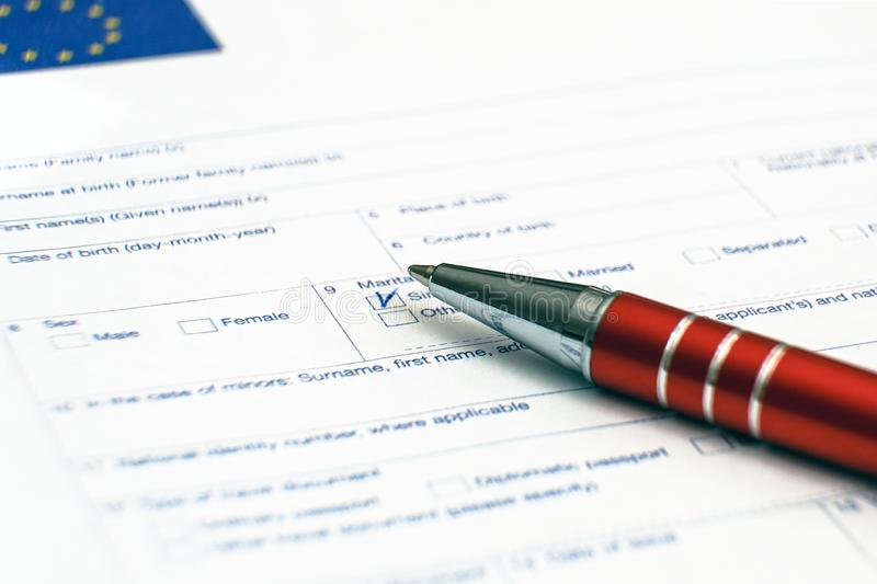 Schengen visum, frågeformulär Hand med pennan som avslutar en questionary arkivbild