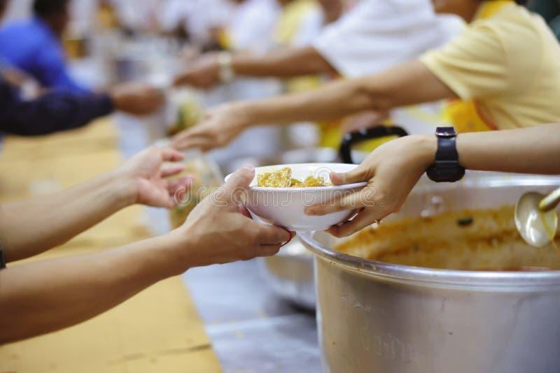Schenk aan de slechte die daklozen, nog in de maatschappij worden gezien: concept liefdadigheidsvoedsel voor de armen stock afbeeldingen