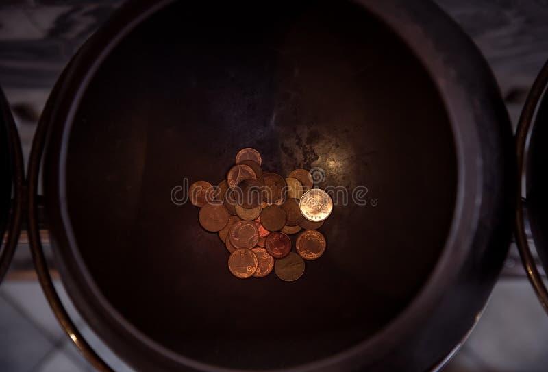 Schenk muntstukken in monniks` s aalmoes-kom stock foto's