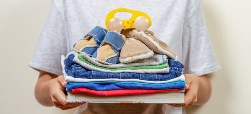 Schenkingsconcept Jong geitjeholding in zijn handenboeken, kleren en speelgoed voor liefdadigheid stock fotografie