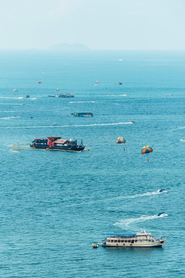 Schepen die over het overzees met toerist drijven die Parasailing in Pattaya, Chonburi, Thailand spelen stock foto