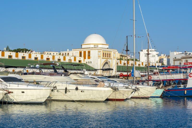 Schepen en boten in Mandraki-haven met Nieuwe markt Nea Agora bij achtergrond, Rhodos, Griekenland stock afbeelding