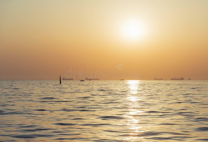 Schepen op weg in zonsopgang stock afbeeldingen