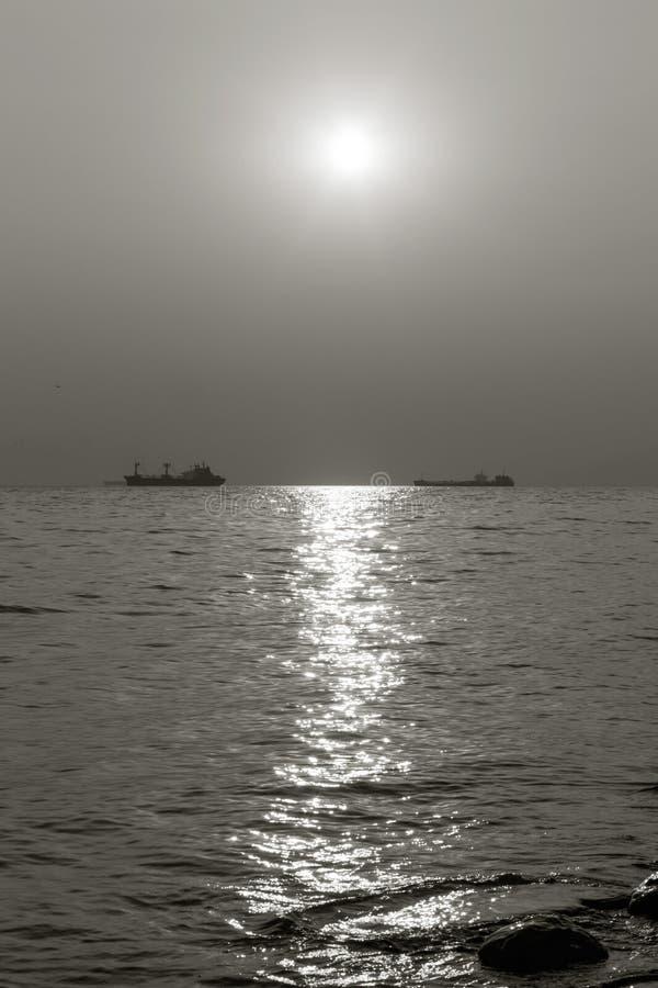 Schepen op zee op de horizon bij zonsondergang stock afbeelding