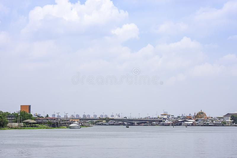 Schepen in van Achtergrond Chao Phraya River en cityscape hemel en wolken die in Pak Kret in Nonthaburi, Thailand kruisen 16 apri stock foto