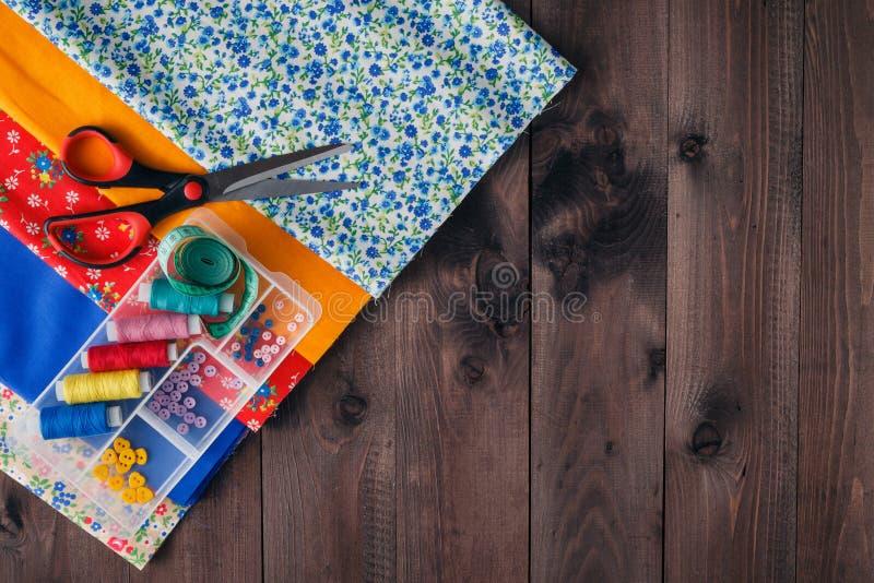 Scheren, Spulen mit Thread und Nadeln, gestreiftes Gewebe stockfoto