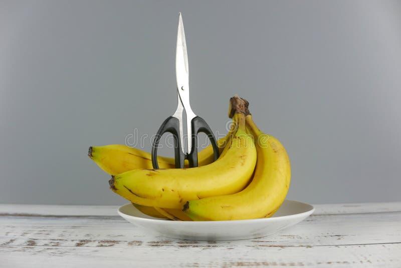 Scheren und Bündel Bananen auf hölzernem Hintergrund Pille im hand stockbilder