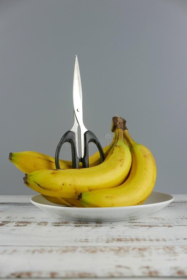 Scheren und Bündel Bananen auf hölzernem Hintergrund Pille im hand Kopieren Sie Raum f?r Text oder Logo Vertikaler Schuss lizenzfreie stockfotografie