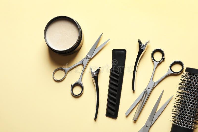 Scheren und die Zusätze anderen Friseurs auf gelbem Hintergrund, flache Lage lizenzfreie stockfotografie