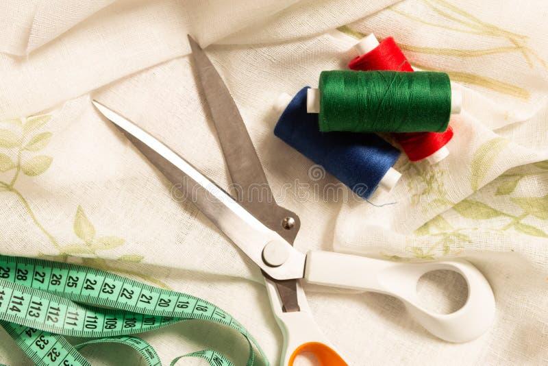 Scheren und Fadenspule auf Gewebe stockfotografie