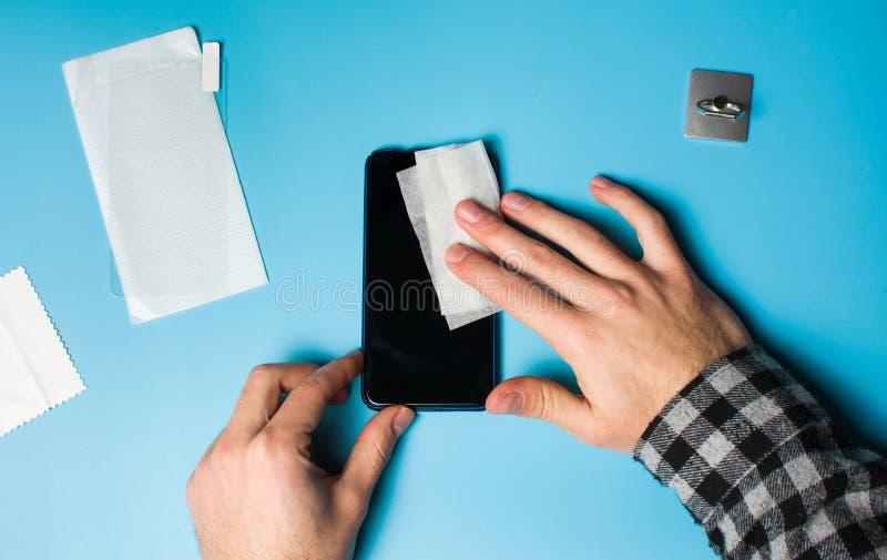 Scherm van de mensen het schoonmakende telefoon om beschermend glas toe te passen royalty-vrije stock afbeelding