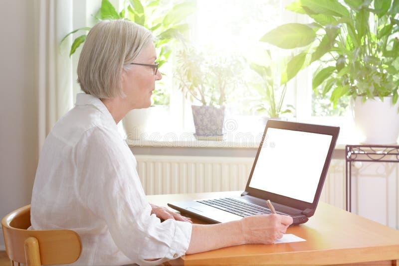 Schermo in bianco del computer portatile senior della donna immagini stock libere da diritti