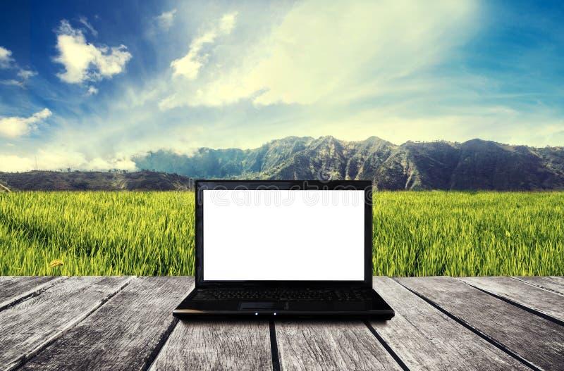 Schermo bianco in bianco del computer portatile, sulla tavola di legno alla campagna Schermo di computer del percorso di ritaglio fotografia stock