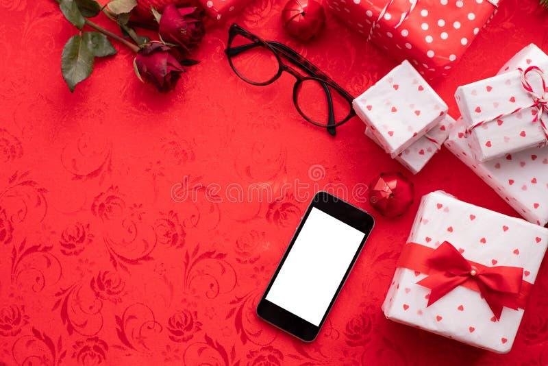 Schermo in bianco sullo Smart Phone con il fondo rosso della tovaglia Fondo di celebrazione di San Valentino immagine stock libera da diritti