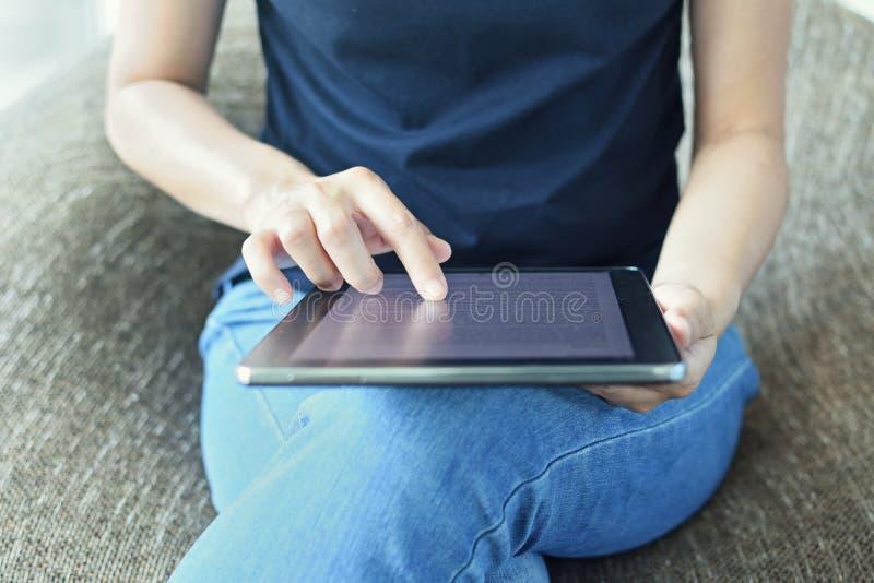 Schermo commovente del dito della donna di una compressa digitale fotografie stock