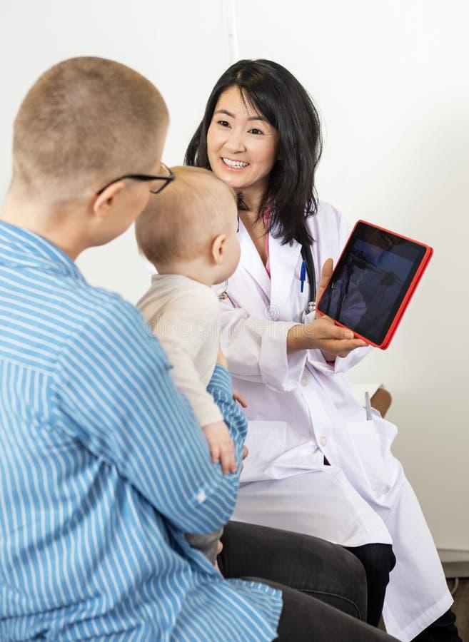 Schermo del dottore Show Digital Tablet alla donna con il bambino immagini stock libere da diritti