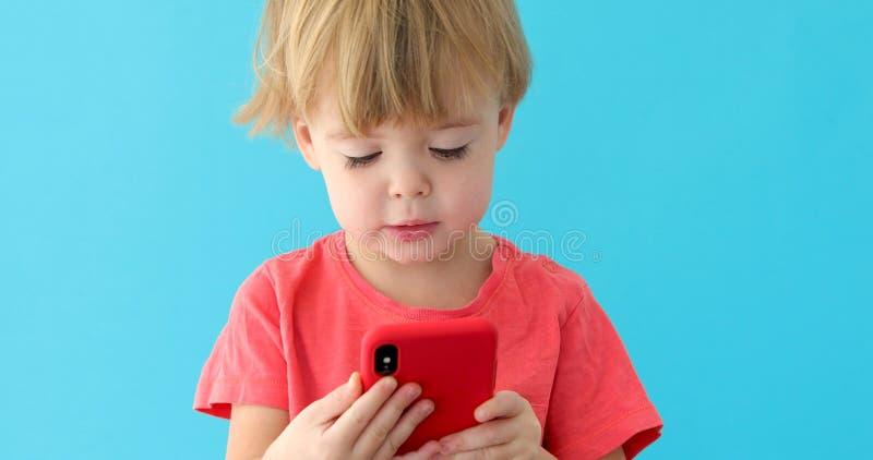 Schermo di spillatura del telefono cellulare del bambino, interesse nella tecnologia moderna immagine stock libera da diritti