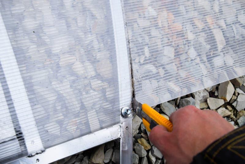 Scherp polycarbonaat wanneer het installeren van het op de kaderelementen van de serre Serreinstallatie royalty-vrije stock foto