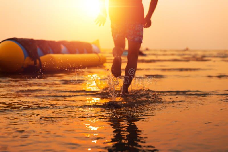 Scherp voorwater en onduidelijk beeldkind die met waterplons lopen stock afbeeldingen