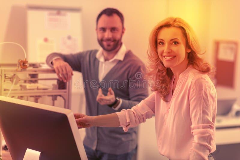Scherpe collega's die gelukkig voor de camera na een taaie dag stellen stock afbeelding