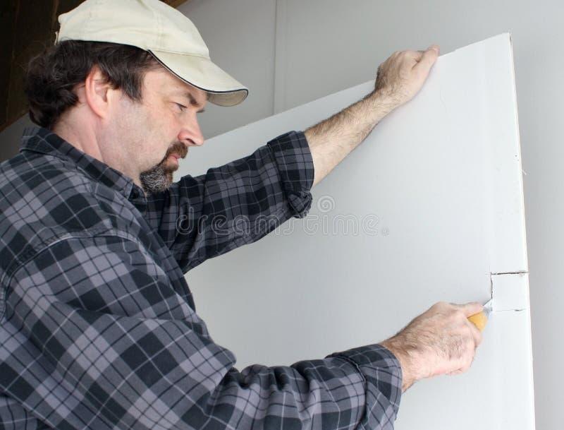 Scherpe drywall van de mens stock afbeelding