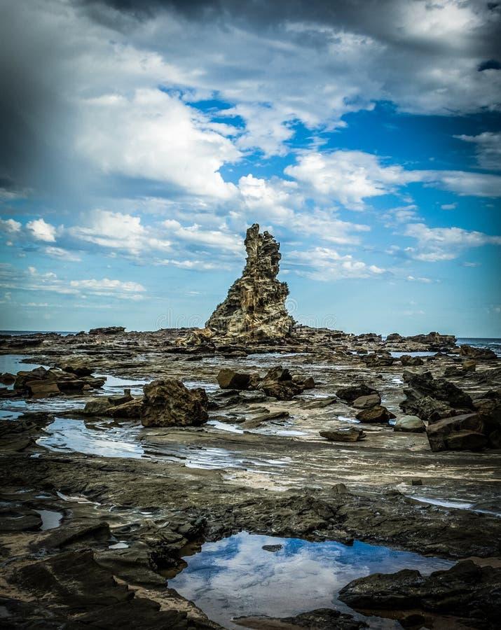 scherpe en ruwe klippenrotsen die uit het water van de Australische kustlijn te voorschijn komen stock afbeeldingen