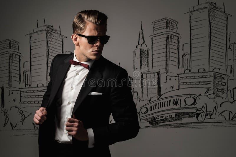 Scherpe geklede mens in zwart kostuum tegen stad stock afbeelding