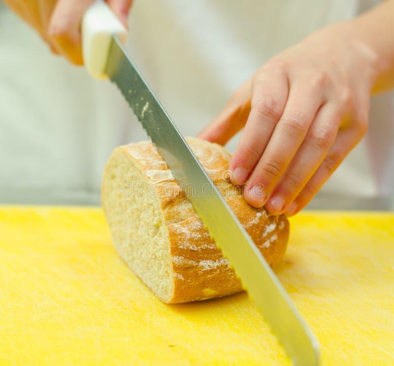 Scherpe plakken van brood van broodzitting op gele oppervlakte, hand die groot mes houden royalty-vrije stock afbeeldingen