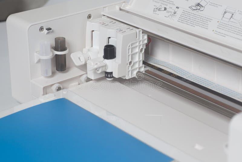 Scherpe plotter met blauw document stock afbeelding
