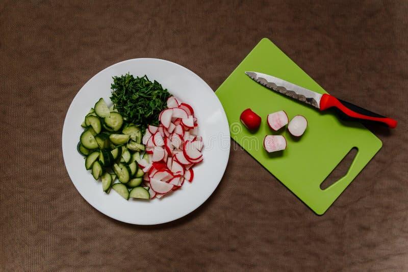 Scherpe Raad, mes en gehakte radijs, komkommer, groene uien stock foto