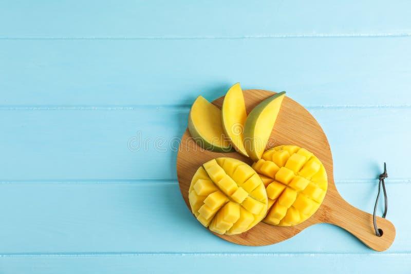 Scherpe raad met besnoeiings rijpe mango's op kleurenachtergrond royalty-vrije stock fotografie
