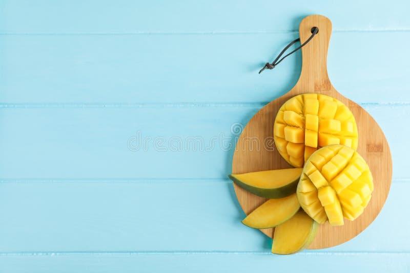 Scherpe raad met besnoeiings rijpe mango's op kleurenachtergrond stock fotografie