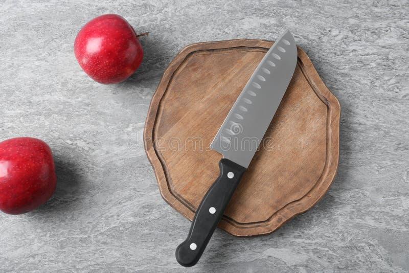 Scherpe raad met het mes van de chef-kok en appelen op grijze achtergrond royalty-vrije stock foto