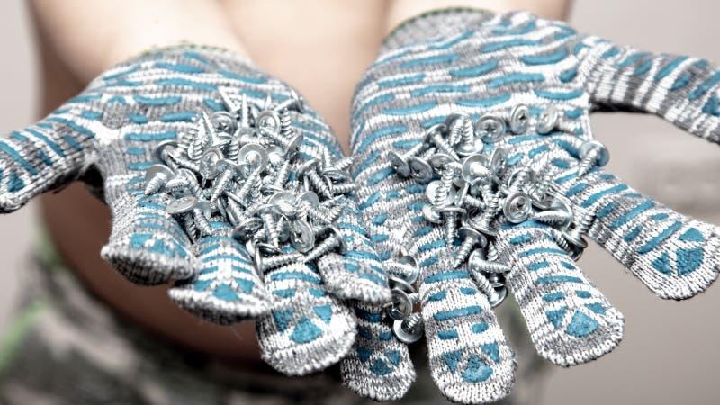 Scherpe schroeven in de bouw van handschoenen stock fotografie