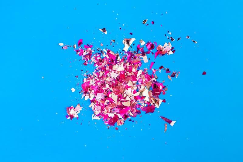 Scherven van slanke lovertjes een gebroken gebrandschilderd glas op een heldere blauwe achtergrond, stock afbeelding