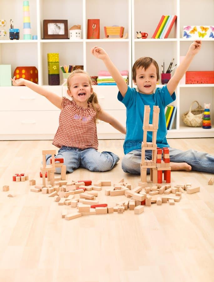 Scherza fiero delle loro costruzioni di legno del blocco immagine stock