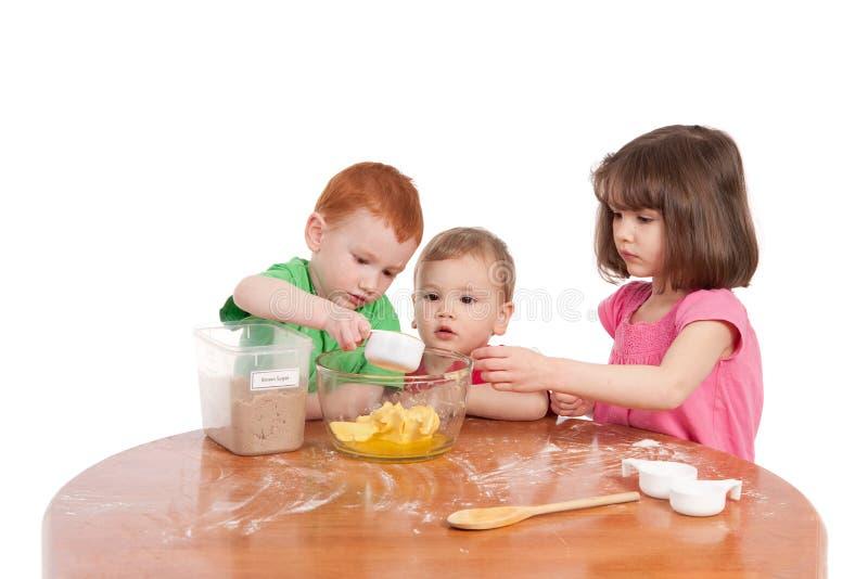 Scherza gli ingredienti di misurazione per cuocere nella cucina immagini stock libere da diritti