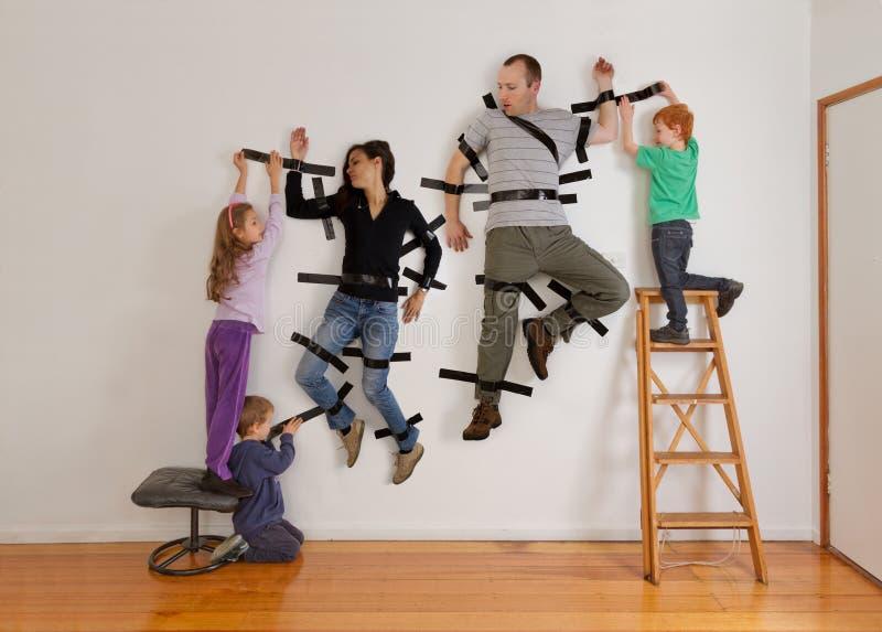 Scherza il lavoro di squadra che lega i genitori con un nastro per murare fotografie stock libere da diritti