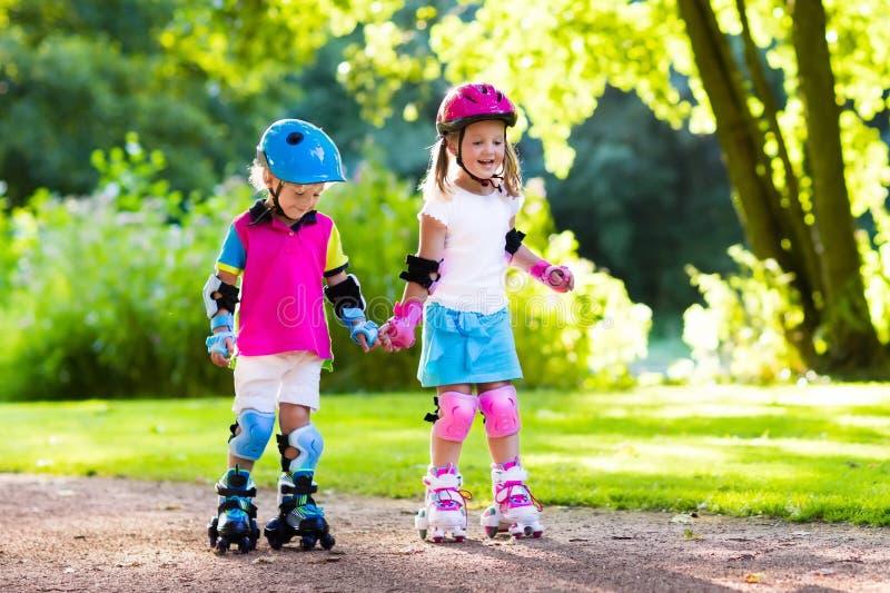 Scherza il pattinaggio a rotelle nel parco dell'estate fotografia stock