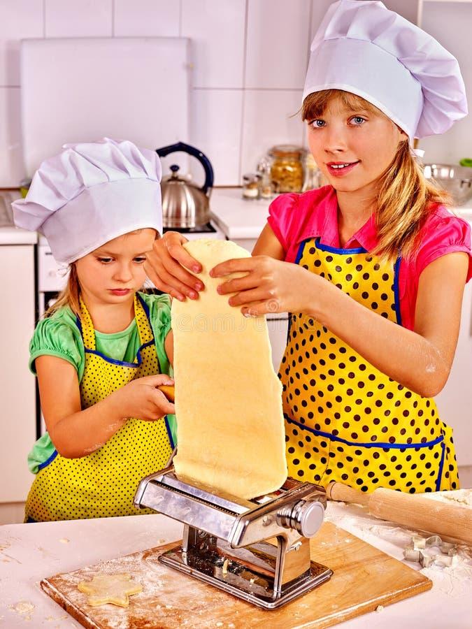Scherza la ragazza che produce la pasta casalinga alla cucina fotografie stock libere da diritti