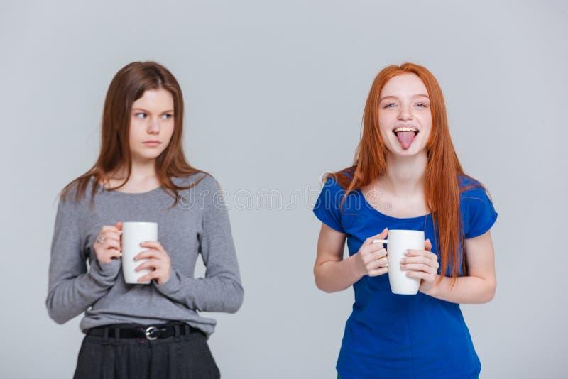 Scherzare felice due e giovani donne aggrottanti le sopracciglia tristi che bevono tè fotografia stock