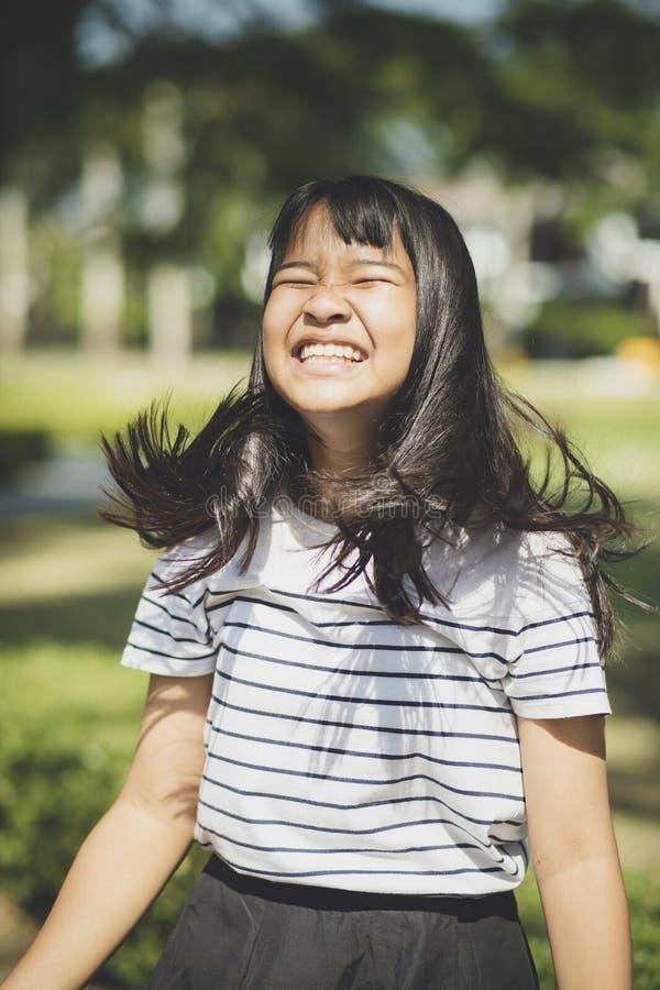 Scherzare fronte dei capelli asiatici del perno d'arresto degli showns dell'adolescente che scorrono da w immagini stock libere da diritti