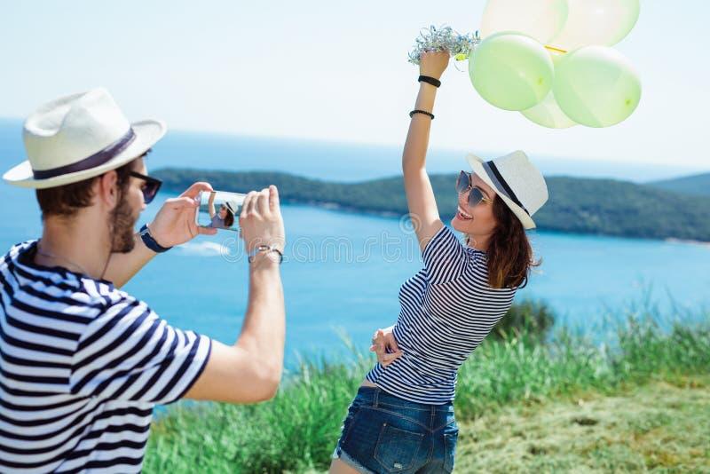 Scherzare turistico e fotografare la sua amica durante le vacanze estive fotografia stock libera da diritti