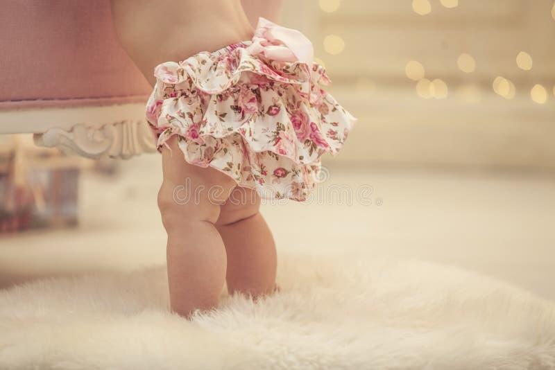 Scherzen Sie Baby in der rosa Kleidung und im glücklichen Innenraum lizenzfreies stockfoto