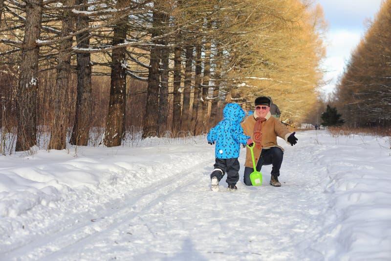 Scherzen Sie Betrieb im Winterpark und haben Sie Spaß mit Familie stockfotos