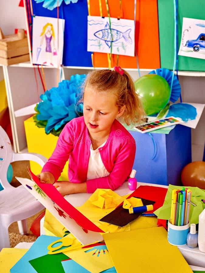 Scherzen Sie das Halten des farbigen Papiers auf Tabelle im Kindergarten lizenzfreie stockbilder