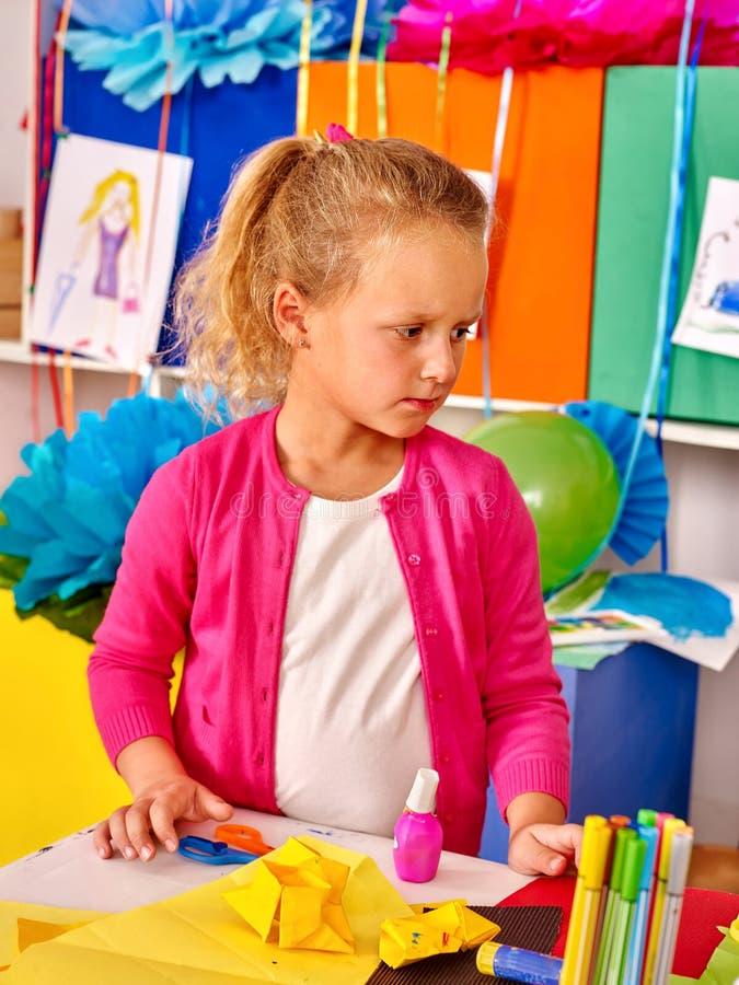 Scherzen Sie das Halten des farbigen Papiers auf Tabelle im Kindergarten stockfotografie
